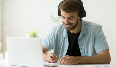 Young man in headphones working at a laptop
