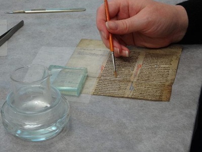 A torn piece of parchment is treated with isinglass