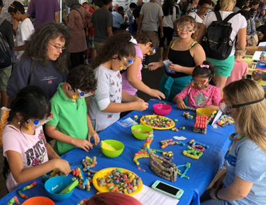 Kids and parents at a table at an outreach event