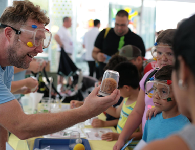 Activity facilitator holds up a jar for a group of kids wearing safety goggles to examine