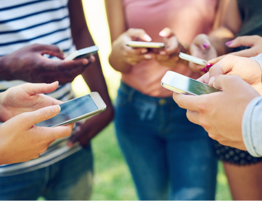 A group of young people standing in a circle with their cell phones out