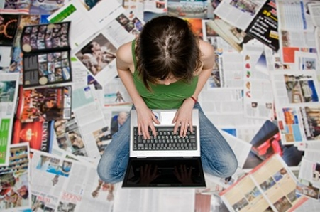 girl with laptop  sitting on magazines