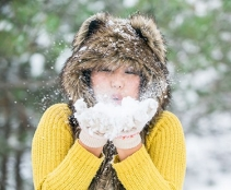 girl blowing handful of snow