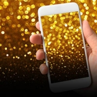 hand holding cell phone with gold sparkles