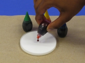 Adding one drop of food coloring to shallow container of glue.