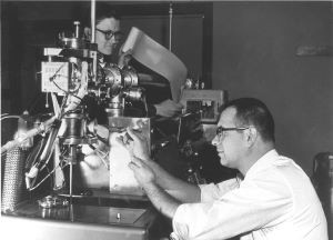 Fred McLafferty and Roland Gohlke (in foreground) work on a Bendix mass spectrometer at Dow circa 1960.