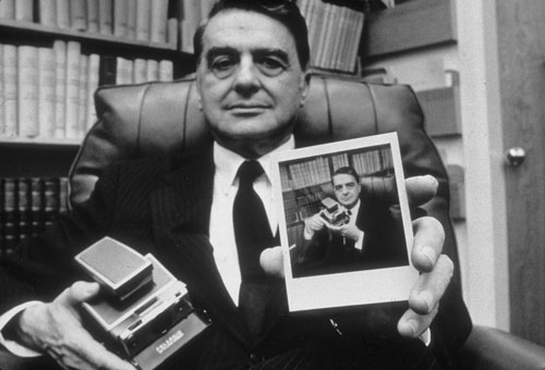 Edwin land inventor of instant photography holds a polaroid sx 70 camera and photograph