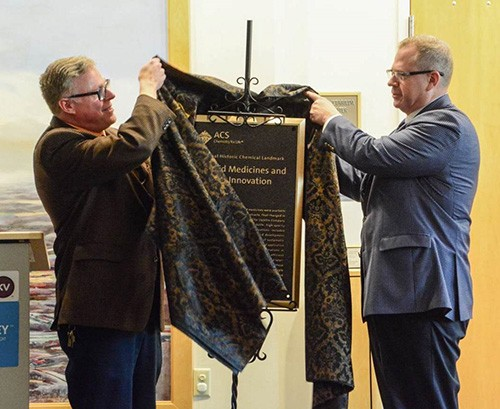 Kalamazoo Valley Museum Director Bill McElhone (left) and ACS Past-President Peter Dorhout unveil the Landmark plaque at the designation ceremony.