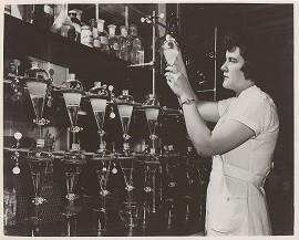Female Upjohn chemist with glass flasks containing steroid intermediates produced by microorganisms