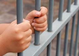 Hands grasping prison bars.