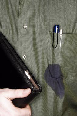 A blue ink pen leaks in the pocket of a dark green shirt.